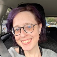 a purple haired woman with glasses smiles at the camera