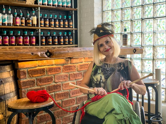 Wheelchair fashion blogger knitting in distillery
