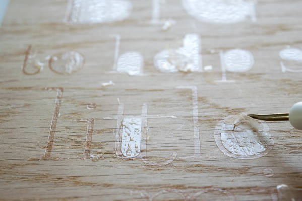 Remove any excess glue flakes from the stencil of the teacher sign.