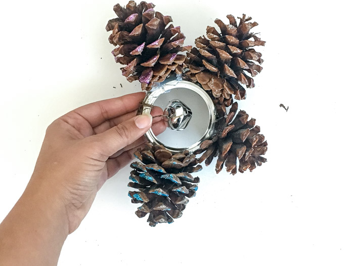 Adding a bell to a pinecone door hanger