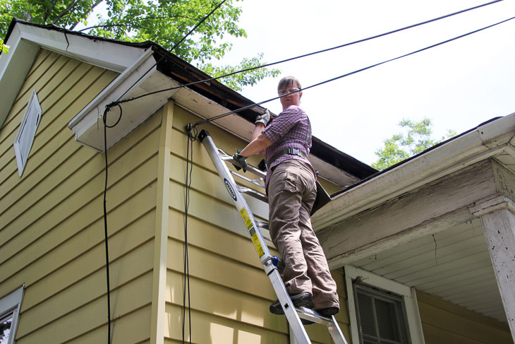 phg woman on ladder looking at low voltage lines