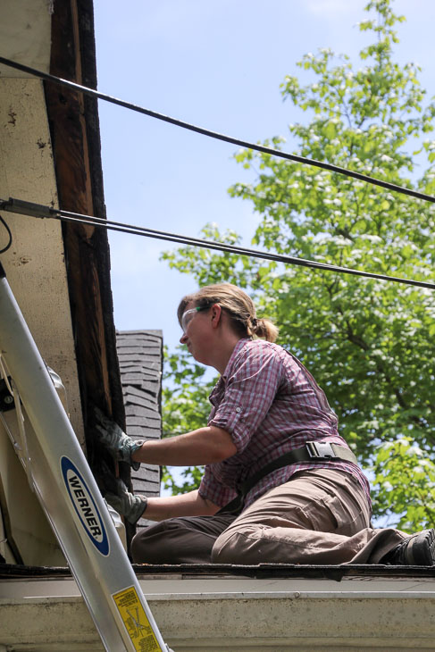 woman on porch roof removing soffit board