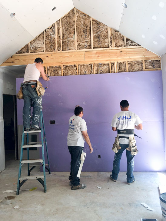 three guys installing purple drywall