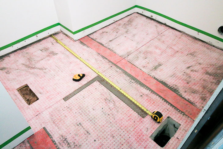 Installed uncoupling mats, finding center of room. Marking perpendicular lines.