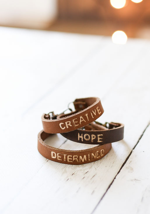 "golden tan and dark tan leather bracelets with ""creative"", ""hope"", and ""determined"" stamped on them."