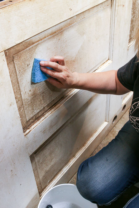 Cleaning Front Door with sponge and soapy water