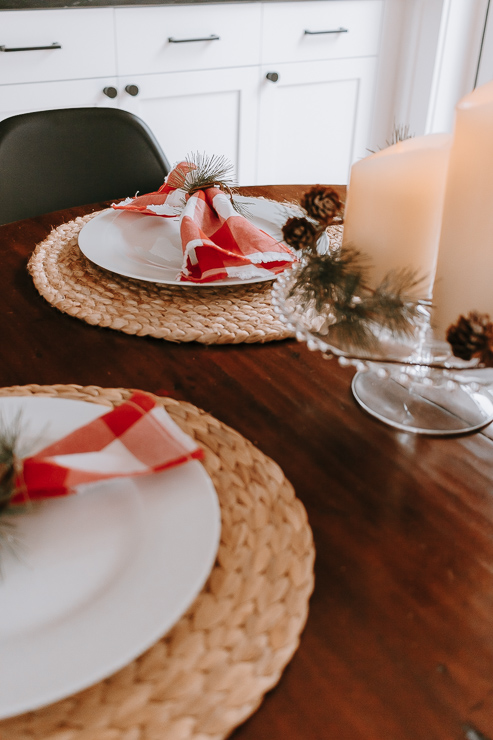 Christmas Table with candles and red napkins and festive napkin rings