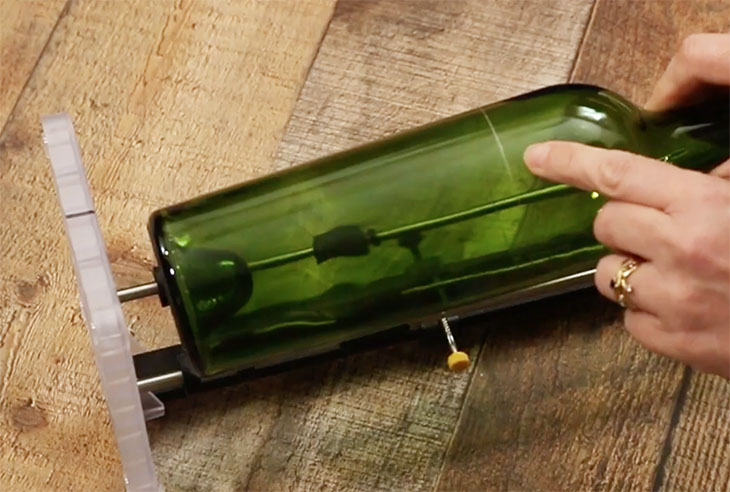 pointing out scored cut line on wine bottle