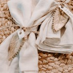 view of napkins tied with jute twine and a clay leaf place card