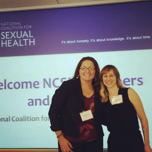 """NSVRC's Jennifer Grove (left) and PreventConnect's Ashley Maier (right) standing and smiling in front of a powerpoint slide projected on a screen that reads """"National Coalition for Sexual Health"""""""