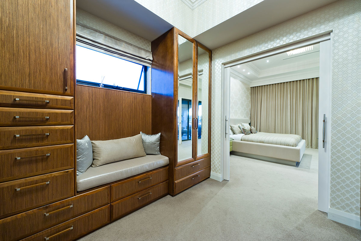 Custom designed walk in robe with seating area and finished in luxury timber