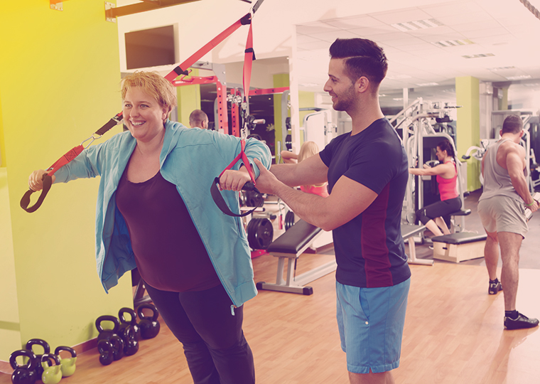 Overweight woman training with personal trainer