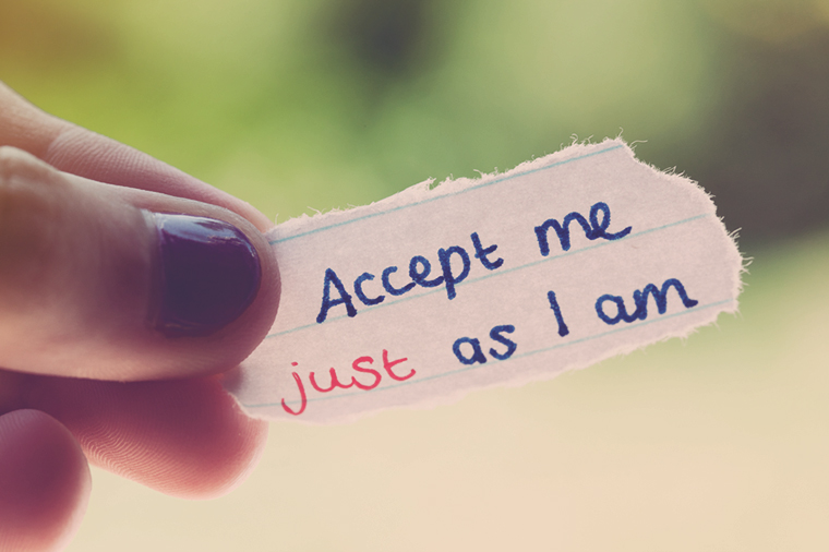 "Girl holds hand-drawn message ""Accept me just as I am"""