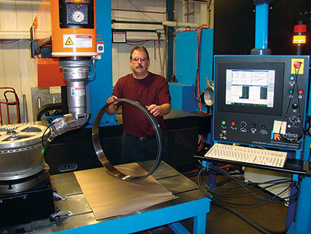 """Scott Stang, Manufacturing Technology Manager for Hi-Tek is pictured with an aerospace engine component processed on the company's newly acquired Laserdyne 795XL Beam Director with fiber laser. The system pictured is equipped with a rotary table which allows drilling """"on-the-fly"""" cooling holes at compound angles at high speed and with high precision."""