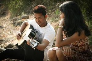 בחור עם גיטרה מנגן ושר לבחורה