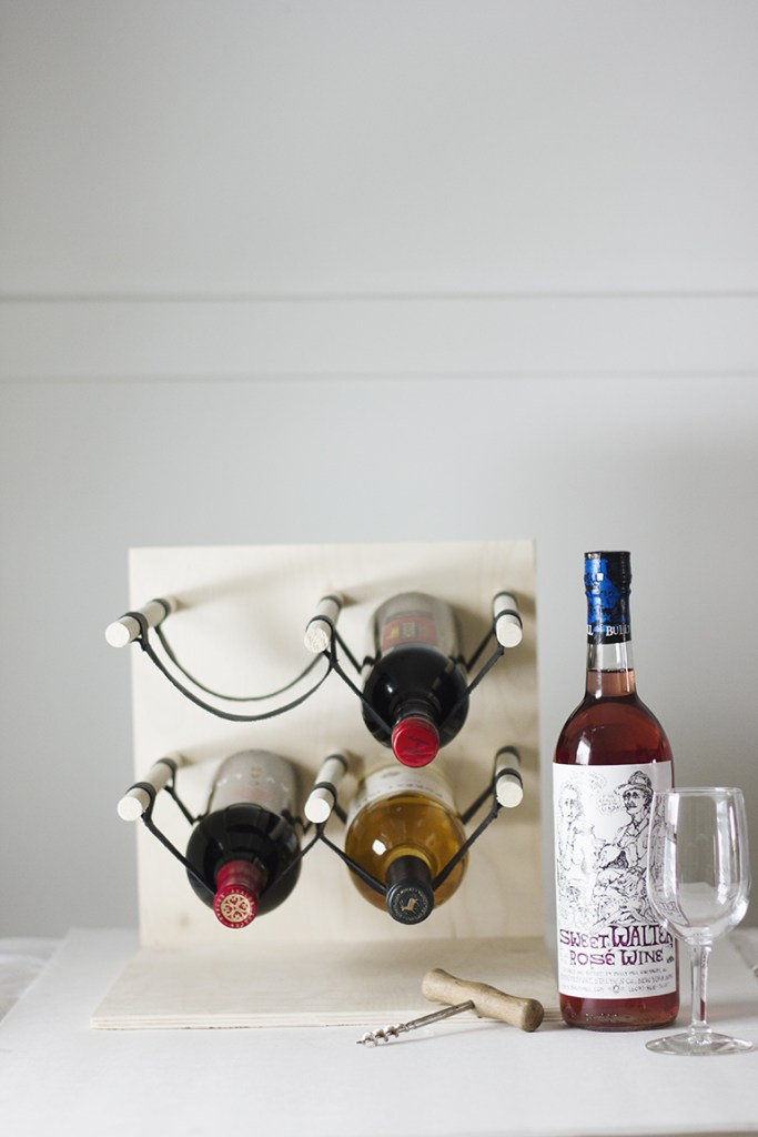 A rope wine rack and wine bottle.
