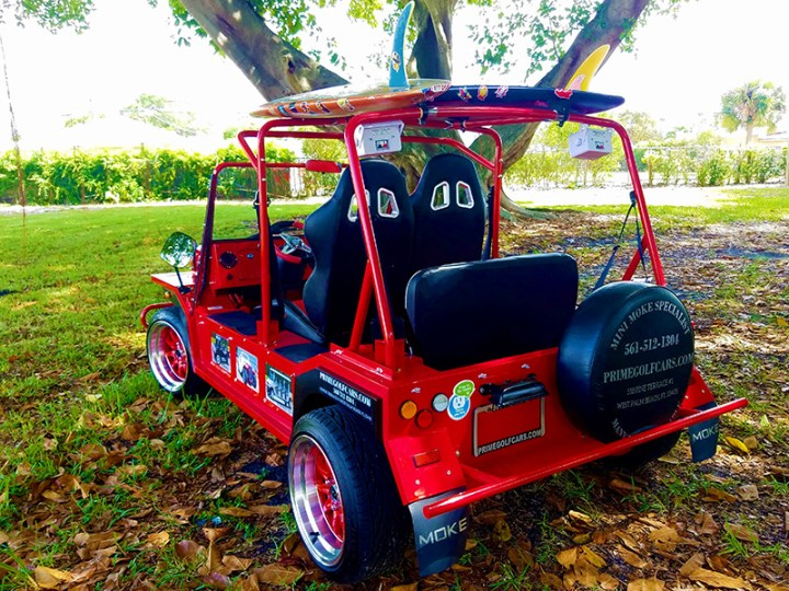 red moke golf car with custom seats custom speakers and custom color wheels