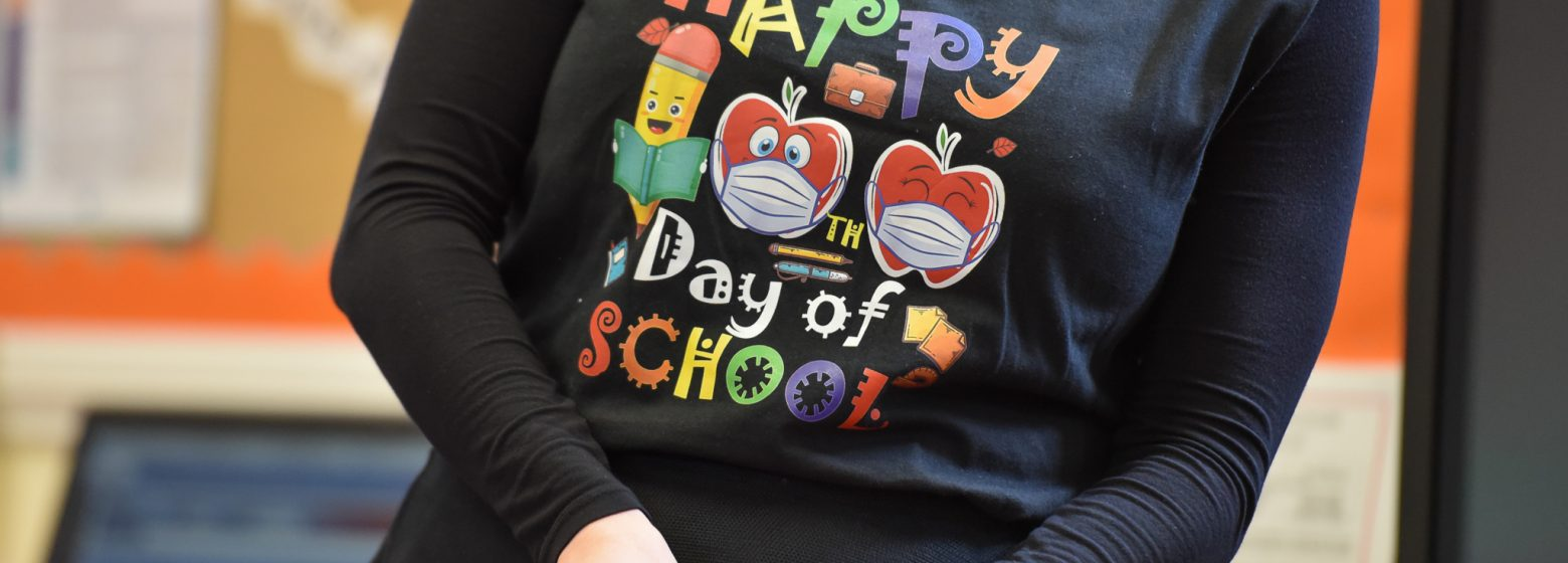 A teacher wearing a t-shirt that says 'Happy Day of School'