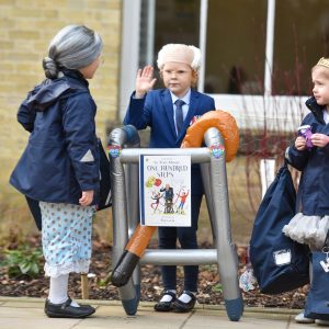 Three kids stood outside school, dressed up as older verisons of themselves.