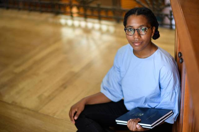 Rosed Serrano sitting on floor holding her senior thesis