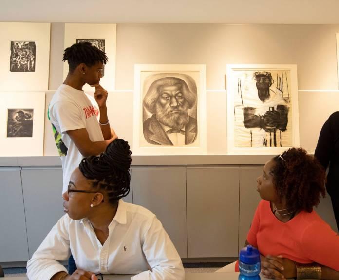 A student contemplates a portrait of Frederick Douglas
