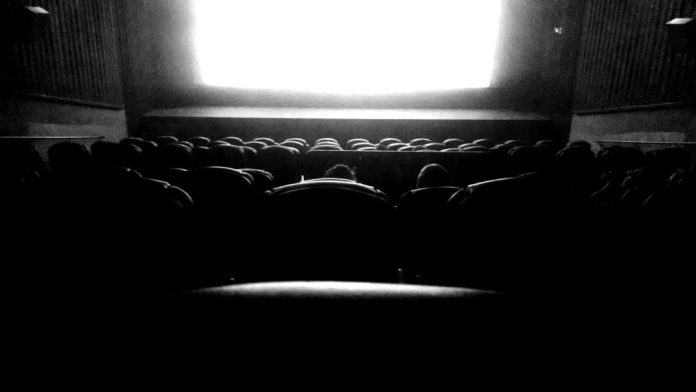 A black-and-white photo of a movie theatre during a film.