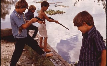 A vintage snapshot of four boys playing with toy guns next to a lake.