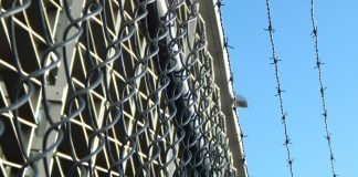A low-angle photo of barbed wire at a prison.