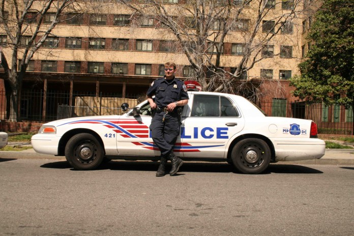 Photograph of a police officer leaning against a police car