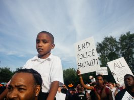 """Photograph of protest with boy in foreground, a sign in the background saying """"end police brutality"""""""