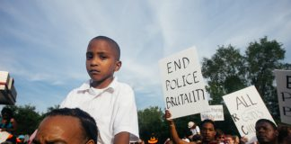 "Photograph of protest with boy in foreground, a sign in the background saying ""end police brutality"""
