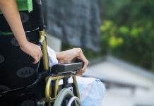 Image of a caretaker wheeling an elderly person in a wheelchair.