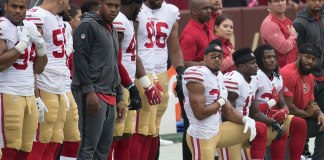 Photo of San Francisco 49ers players kneeling during the National Anthem.