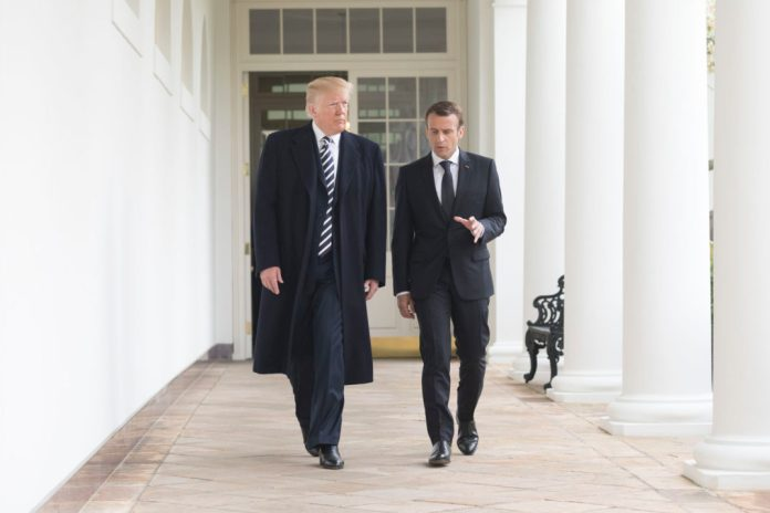 Photograph of President Trump and President Macron walking outside the White House, Macron speaking and gesturing with his hand