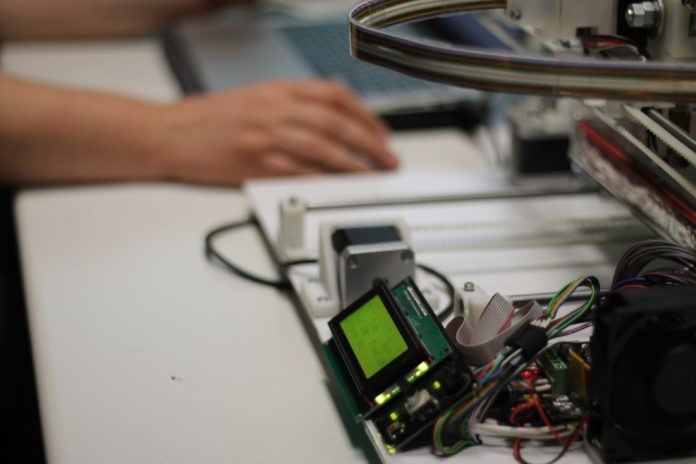 Photograph of a 3D printer with a person's hand on a computer mouse nearby