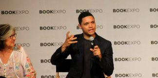 photograph of Trevor Noah speaking into a microphone