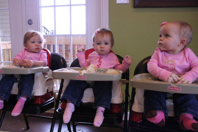 Photograph of three toddlers dressed in pink