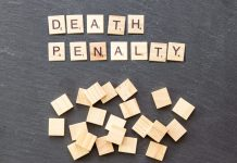 "Scrabble tiles spelling out the phrase ""Death Penalty"" on a gray background"