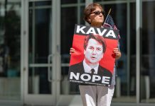 "photograph of a woman holding a sign with the slogan ""kava-nope"" and a picture of Brett Kavanaugh"