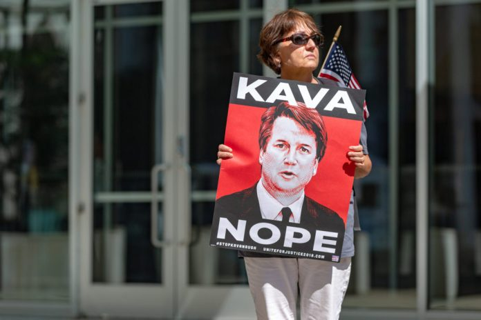 photograph of a woman holding a sign with the slogan