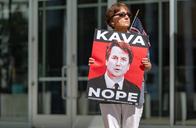 """photograph of a woman holding a sign with the slogan """"kava-nope"""" and a picture of Brett Kavanaugh"""
