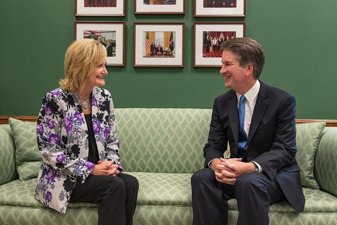 photograph of Mississippi senator Cindy Hyde-Smith and Brett Kavanaugh smiling while sitting on a couch