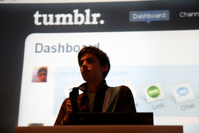 Photo of a man speaking into a microphone, standing in front of a screen displaying a tumblr dashboard