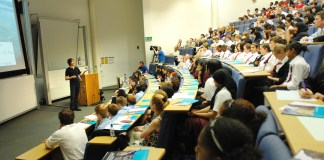 Photograph of a lecturer speaking to a hall of students