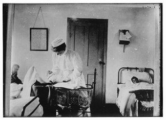 Black and white photograph of a midwife holding a baby