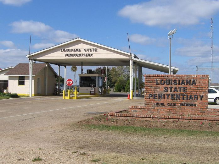Photograph of the entrance to the Louisiana State Penitentiary, showing a stop sign and a guard station along with a sign naming the institution and the warden Burl Cain