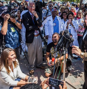 Kamala Harris giving a speech, smiling and speaking into microphones, with people crowded around