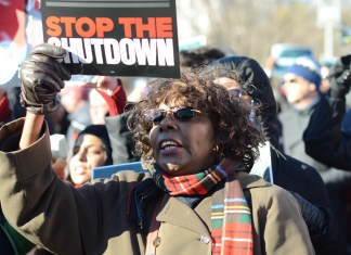 """A woman holding a sign that says """"stop the shutdown"""""""