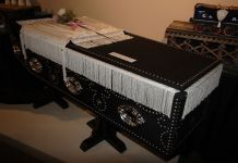 Photograph of a replica of Lincoln's coffin. It is black and draped with white cloth and has a few flowers on top