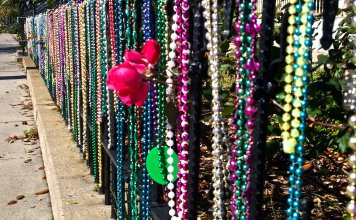 A fence covered in Mardi Gras beads of various colors